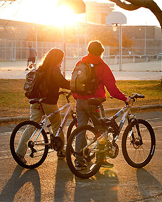 Photo of two students walking their bikes past basketball courts near Bradley Residence Hall.