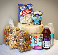 Photo of the items in one of the gift baskets from Fresh Market: three bags of snack mix, two Clif Bars, Microwave popcorn, Ben and Jerry's Icecream and two Vitamin Waters.
