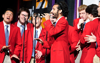 Photo of members of the UW–Madison Mad Hatters a capella group performing at the Kohl Center.