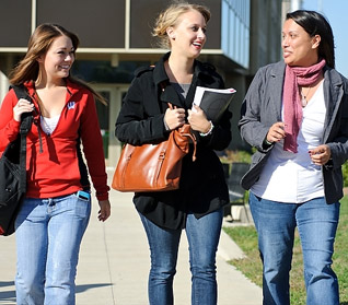 Photo of smiling students outside of Ogg Hall on an autumn morning.