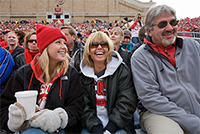 Photo of a UW–Madison student at a Badger Football game with her parents.