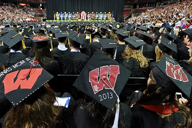 Photo of graduates with decorated graduation caps at commencement.