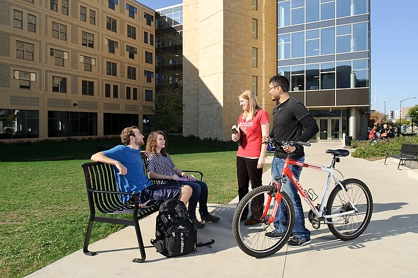 Students socialize in front of Ogg Hall on a sunny autumn morning.
