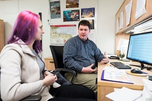 Photo of Brian Asen, biology advisor in the Department of Bacteriology, meeting with a student in his office.