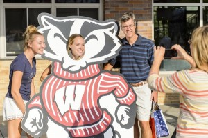 A family poses with a cardboard Bucky during Parents' Weekend.