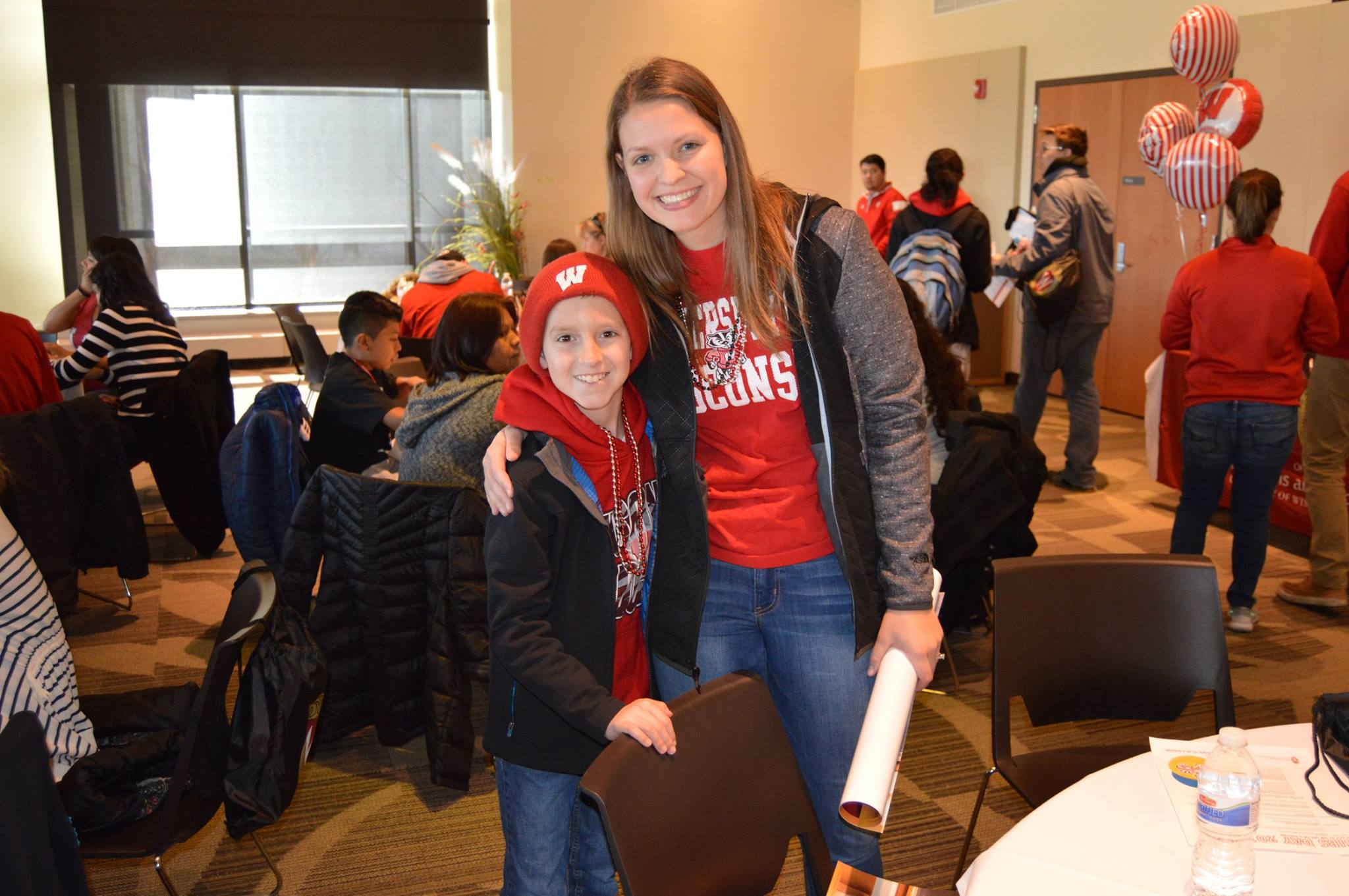 A student and her younger brother smile for the camera during a Sib's Day event.