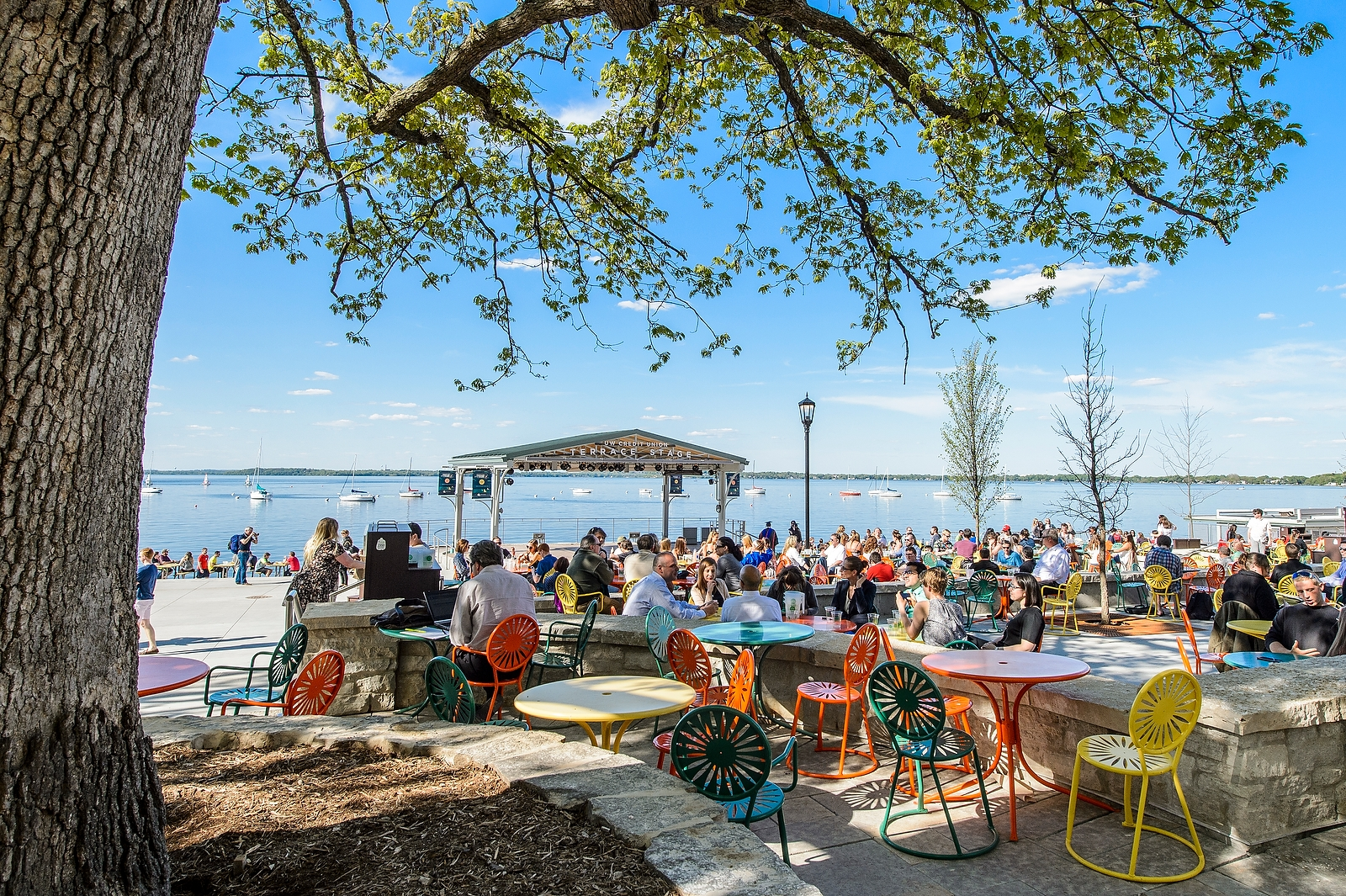 Visitors enjoy the Memorial Union Terrace on a warm spring day, Lake Mendota in the background.