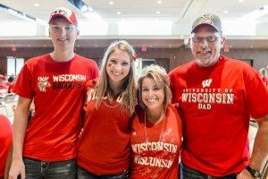 Family dressed in red pose for Parent Program tailgate activity