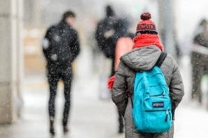 Students wearing winter clothes walk down University Avenue as snow falls.