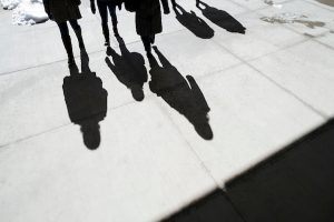 Students cast shadows on the pavement on a sunny winter day on the UW–Madison campus.