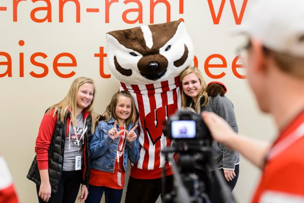 A family of three siblings take a picture with Bucky the Badger, with a cameraperson shown in the foreground.