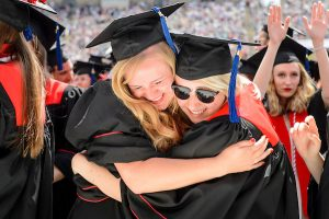 Two graduates share an emotional hug at the conclusion of a UW–Madison spring commencement ceremony at Camp Randall Stadium.