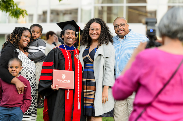 A graduate poses with family following spring commencement.