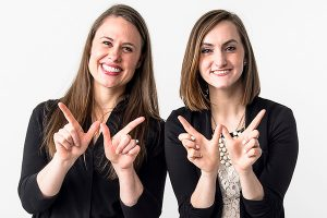 """Stephanie Benson-Gonzales and Monica Ruppert of the Parent and Family Program, displaying the """"w"""" sign."""