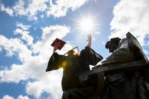 Wearing a graduation cap and gown, a soon-to-be-graduate holds a diploma cover overhead as she sits in silhouette in the lap of the Abraham Lincoln statue in front of Bascom Hall.