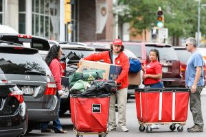Students and their families move belongings between Witte Residence Hall and their car during moving time.