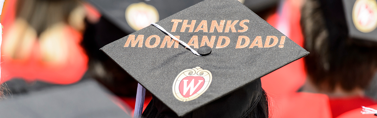 Graduates display personal messages on their graduation caps during UW-Madison's spring commencement ceremony at Camp Randall Stadium.