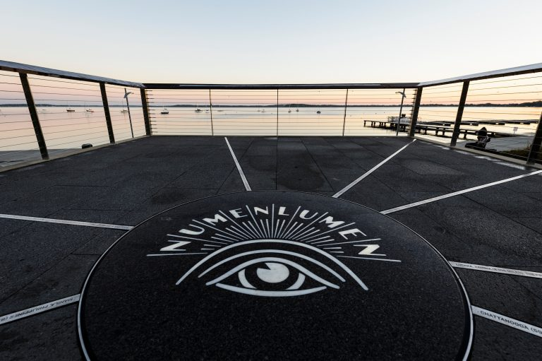 A backlit logo of the university's Numen Lumen seal is pictured in a dawn view of Lake Mendota from Alumni Park's Progress Point.