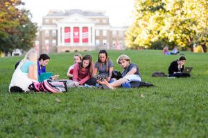 A group of students relax and study on Bascom Hill in autumn.