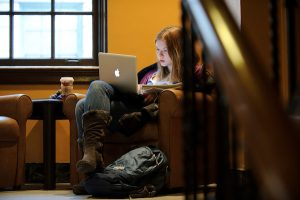 Seated in an armchair, an undergraduate student works on her laptop computer while enjoying the quiet of a tucked-away spot in a staircase landing at the Memorial Union.