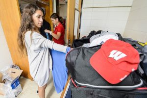 A student is shown with a cart of belongings in a residence hall, her mom helping to hang up clothes in the background.