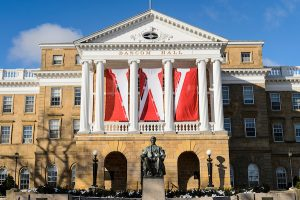 """Bascom Hall with large red and white """"W"""" banners draped between the columns."""