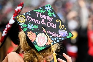 """A graduation cap displaying a personal message of """"thanks mom and dad""""."""
