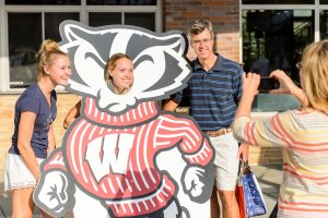 A UW student and her family pose with a large Bucky cut-out for a photo outside of Union South.