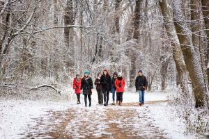 A group of students walk amid snow-dusted trees along a lakeshore path on Picnic Point in winter.