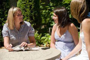 Three female students talking outside the Pi Beta Phi sorority house.