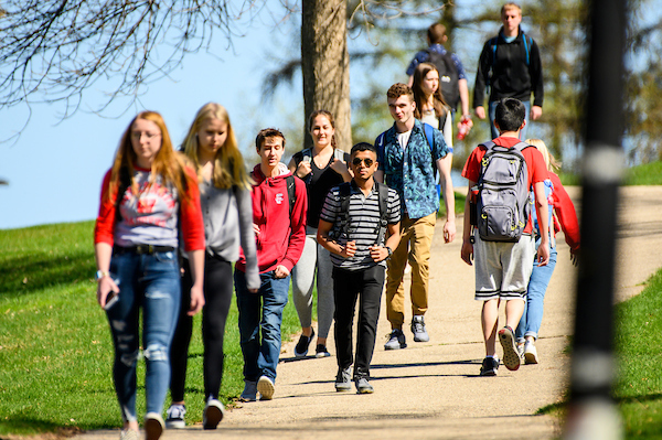UW students walk along a pathway near Observatory Hill on a warm spring day.