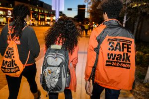 SAFEwalk staff walk with a student to a campus location at night.