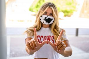 A student wearing a face mask makes the Wisconsin W sign with her hands.