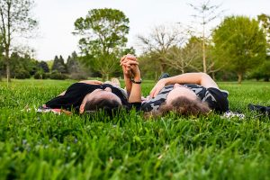 Two students lie in the grass holding hands among the flowering trees and fresh blossoms at the Longenecker Horticulture Gardens.