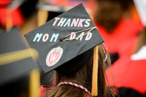 A student displays a personal message, 'Thanks Mom & Dad', on her graduation cap during the spring commencement ceremony.