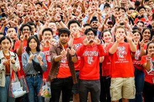 Several dozens UW–Madison students dressed in Badger gear make the W sign.
