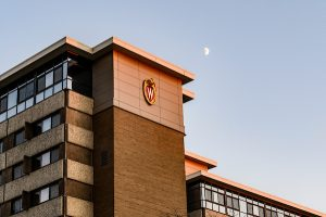The moon rises over the W crest adorning the west side of Witte Residence Hall as sun sets on the UW–Madison campus.