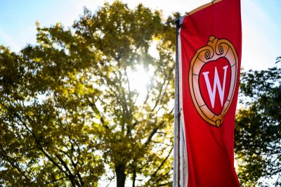 A W crest banner flutters in front of trees on Bascom Hill at the University of Wisconsin-Madison