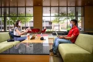 Two students, socially distanced and wearing face masks, study on couches in the Discovery Building at UW-Madison.