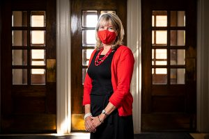 Vice Chancellor for Student Affairs Lori Reesor, wearing a red sweater and mask to match, in Bascom Hall.