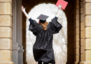 Wearing a graduation cap and gown, a soon-to-be-graduate holds a diploma cover overhead while walking in silhouette through the arched portico of Bascom Hall.