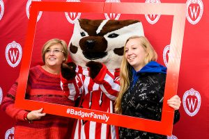 A mother and daughter pose with Bucky in a picture frame with the hashtag Badger Family.