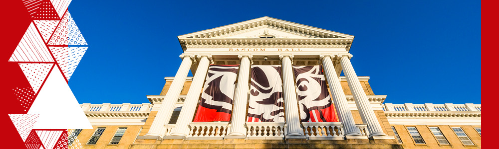 An up-close view of Bascom Hall on a sunny day with Bucky Badger flags between the columns of the hall.